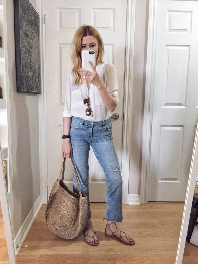 I am wearing HIghwaist bootcut jeans, a white blouse, Madewell Boardwalk sandals, and a large circle bag.