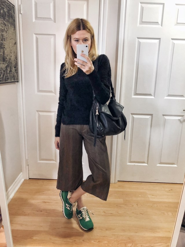 I'm wearing culottes, a black fuzzy sweater, and green new balance sneakers.
