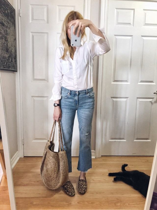 I am wearing a white blouse, cropped jeans, animal print loafers, and a large woven tote.