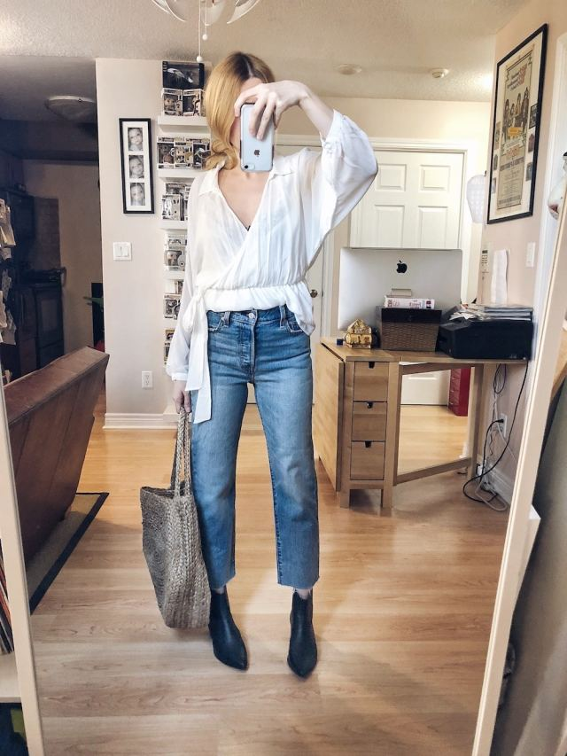 I am wearing a white, faux wrap blouse, Levi's Wedgie Straight Jeans, Black booties, and a large woven tote.