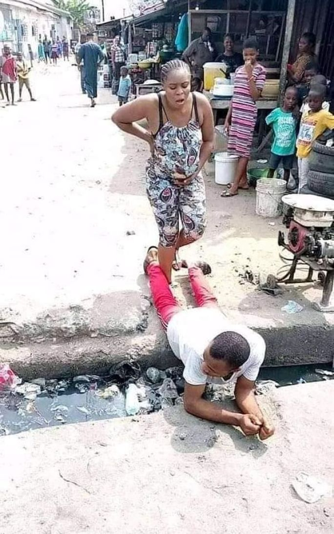 Man Lies On A Gutter For His Pregnant Wife To Pass (Photos)