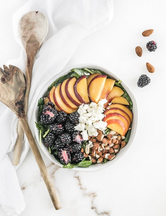This delicious Blackberry Peach Kale Salad is a great way to eat summer fruit! With toasted almonds, goat cheese, mint and a lemon poppy seed vinaigrette, it's a perfect light lunch or side dish! (#glutenfree, #vegetarian)   #kalesalad #summersalad   via livelytable.com
