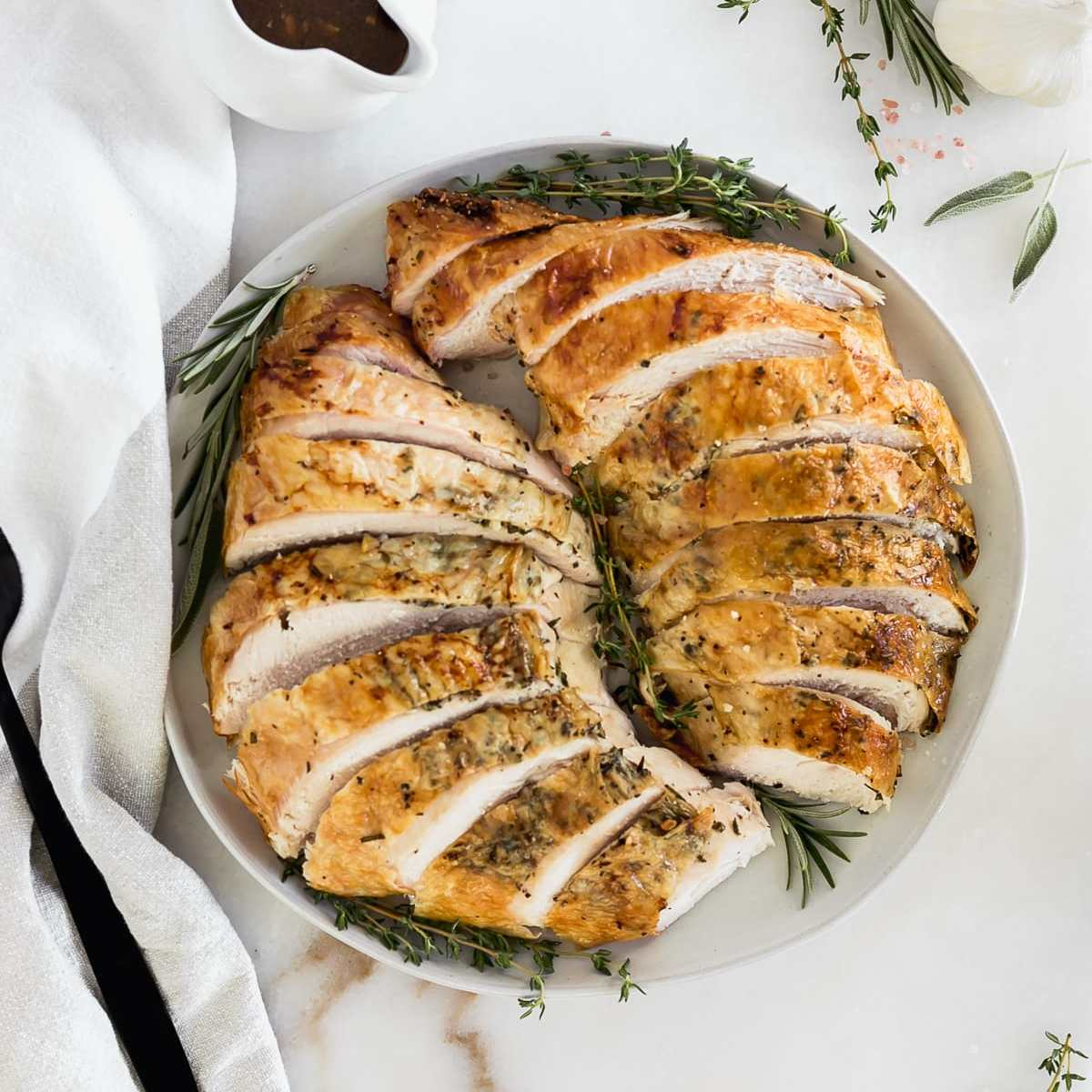 overhead view of sliced roasted bone in turkey breast on a white plate surrounded by fresh herbs.