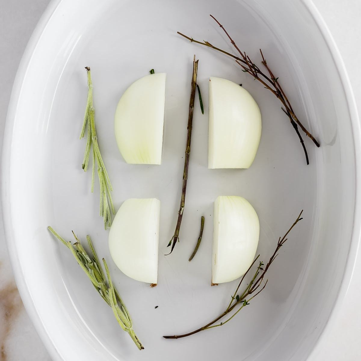 white baking dish with a quartered onion and herb stems in the bottom.