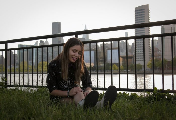 Girl sitting on the grass next to a river with apartment blocks in the background.