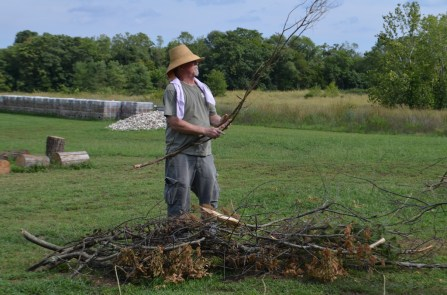 Bill Neff bundles together small branches and other kindling into the lime rick's wick around which all the larger wood will be placed.