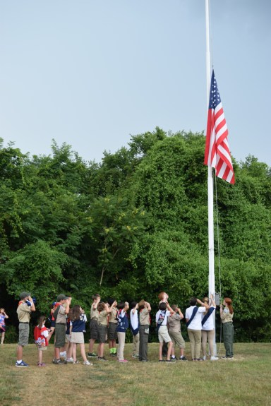 Boys Scouts and American Heritage Girls lower the flag being retired.