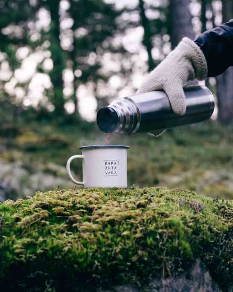 Pouring coffee from a thermos into an enamal mug out in nature.