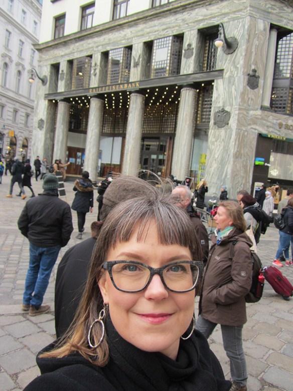 Fotografi som visar Karolina framför byggnader Looshaus i centrala Wien.