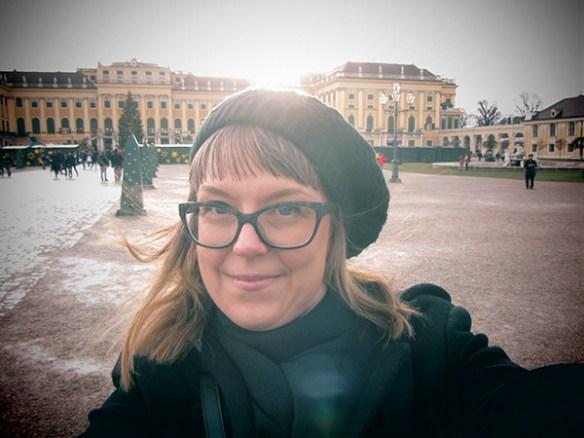 Fotografi som visar Karolina i en selfie framför det gula slottet Schönbrunn.