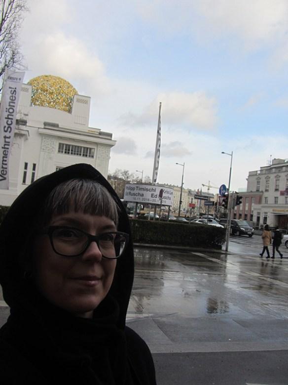Fotografi som visar en mörkt gestalt med kåpa framför byggnaden Secession i Wien.