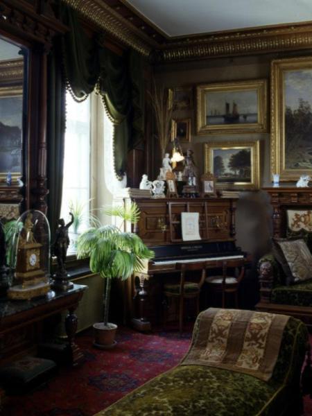 Fotografi som visar hörn av ett rum, som är överlastat med inredningsdetaljer. I hörnet står ett piano.