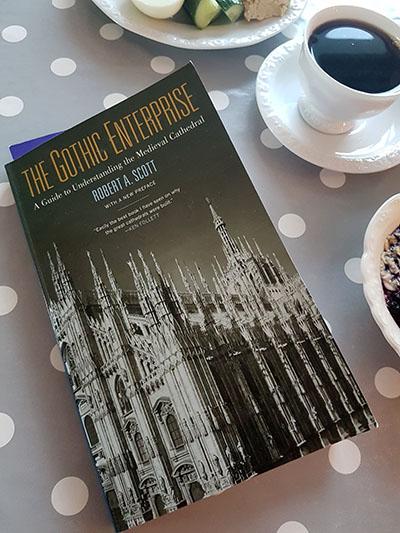 """Fotografi som visar boken """"The Gothic Enterprise"""" på frukostbordet med en kopp kaffe intill."""