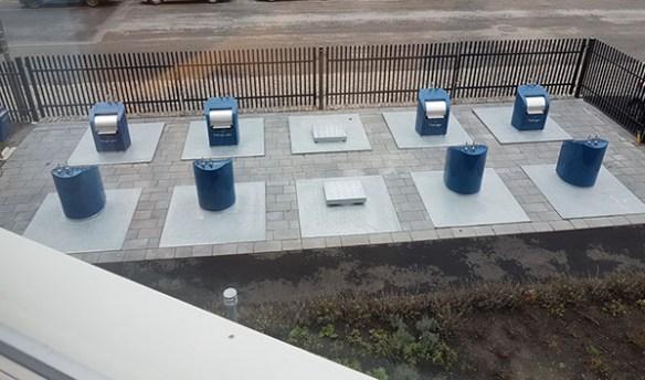 Ett fotografi som visar en toppmoderna, underjordisk återvinningsstation, med smidiga inkastningsluckor ovan jord.