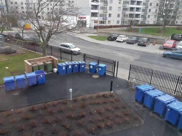 Ett fotografi i fågelperspektiv som visar ett antal blåa plastkärl uppställda på en innergård.