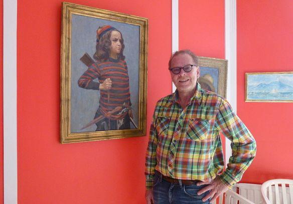 Fotografi som föreställer Antikrundans expert Claes Moser framför en målning som hänger på en röd vägg.