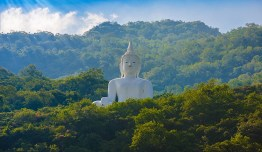 White Buddha statue on the mountain at Wat Thep Phithak Punnaram Nakhon Ratchasima Province, Thailand.