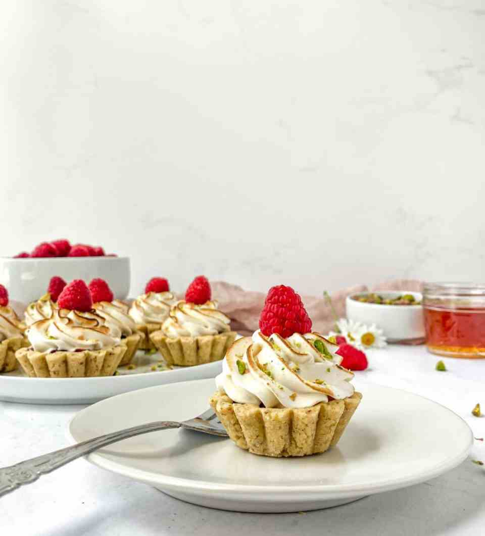 A photo of a raspberry pistachio tartlet on a plate with more tartlets in the background.