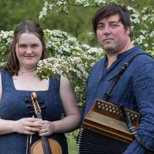 Jackie Oates, who is wearing a blue dress and holding a fiddle, stood beside John Spiers, who is wearing a matching blue shirt and holding a melodeon.
