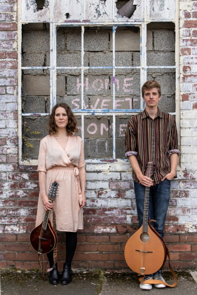 Janice Burns & Jon Doran stood in front of a wall with a window and the spray-painted words 'Home Sweet Home'. Jan is holding a mandolin and Jon is holding a bouzouki.