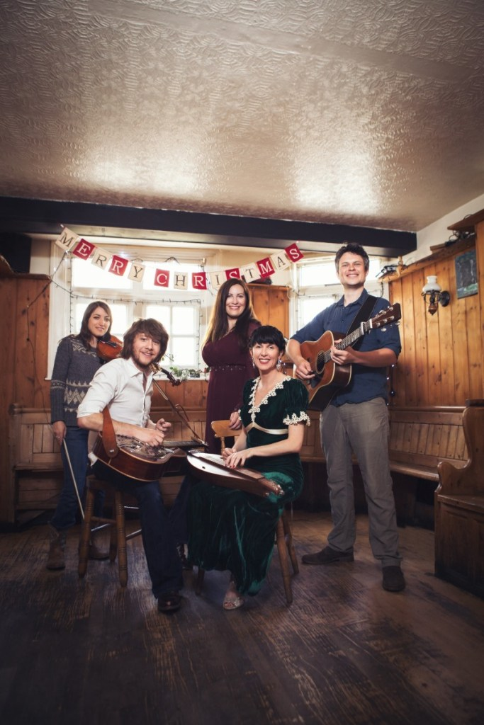 A Winter Union - the band gathered in a pub holding their instruments. There is a banner saying Merry Christmas behind them.