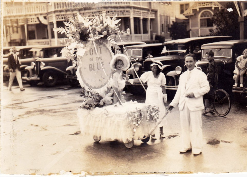 "My grandmother in a baby parade on a flower-covered float called ""Out of the Blue"" wearing a maribou feather diaper cover"