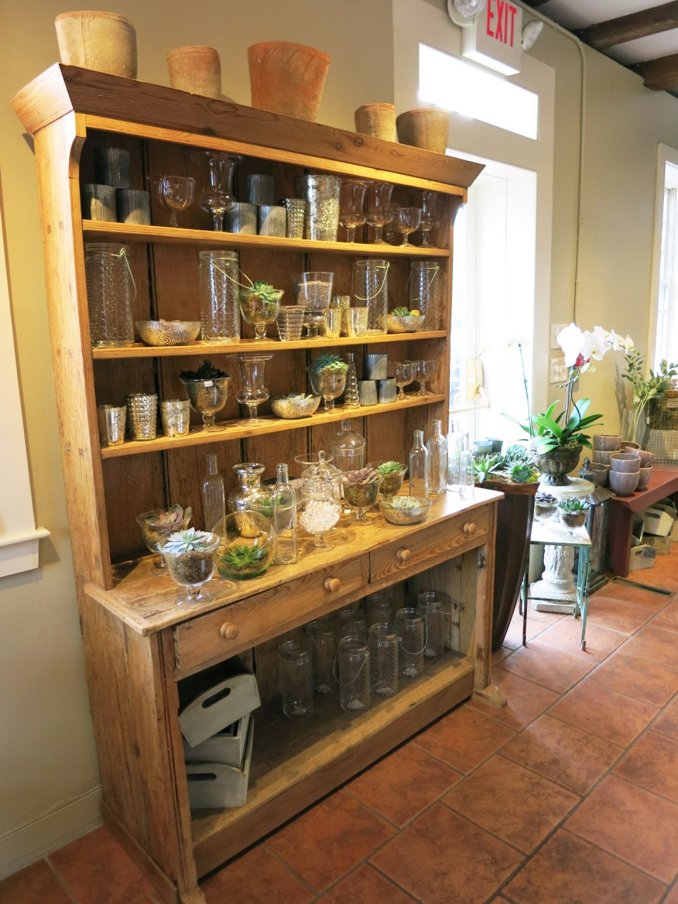 Antique wooden hutch displaying glassware and succulents in Studio 539 located on Wickenden Street in Providence, RI