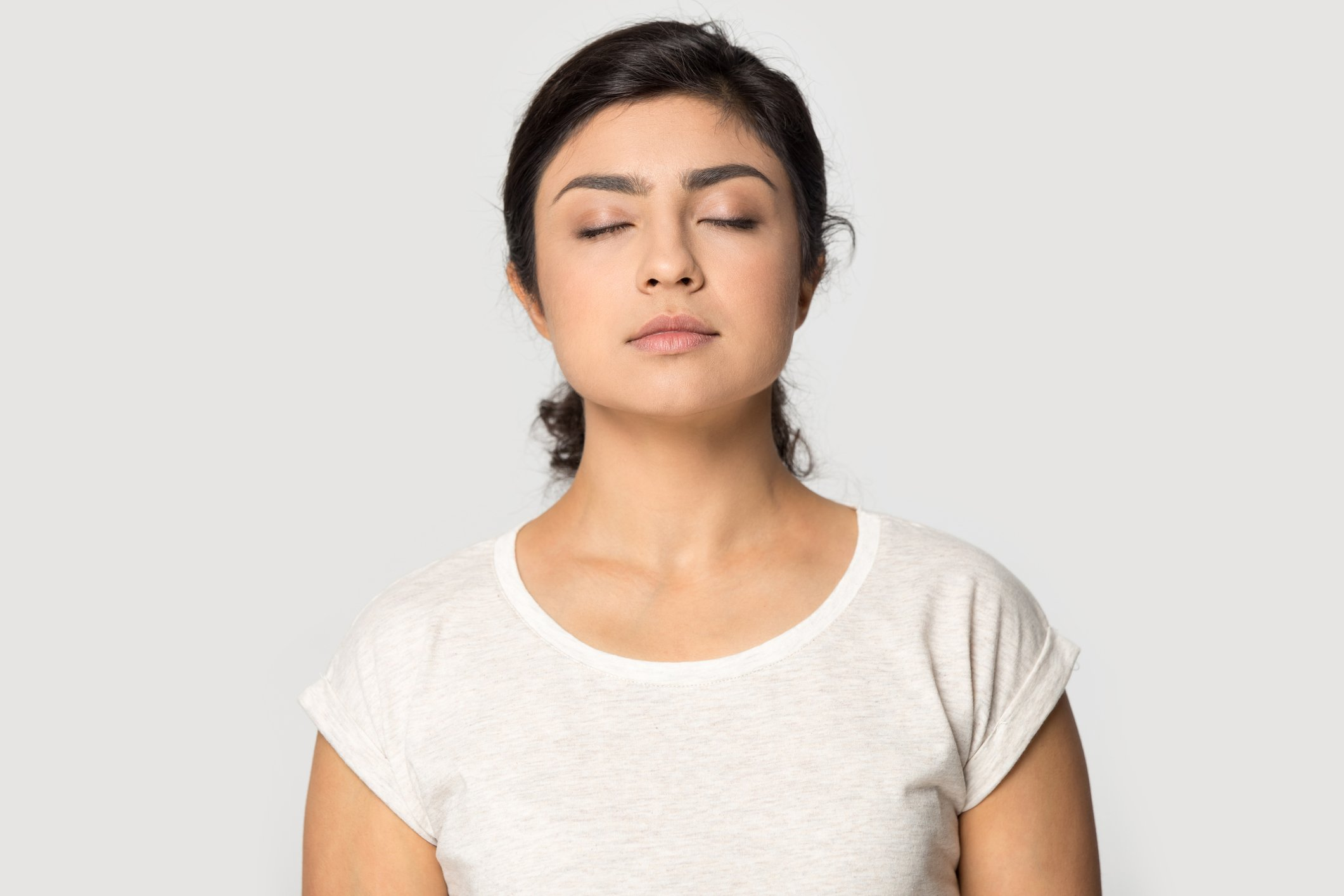 Peaceful millennial indian girl isolated on grey studio background relieve negative emotions breathe fresh air, calm young ethnic woman meditate with eyes closed, stress free, meditation concept