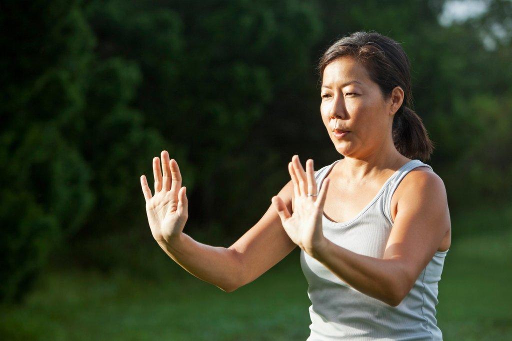 Mature Asian woman (40s) exercising outdoors, practicing tai chi.