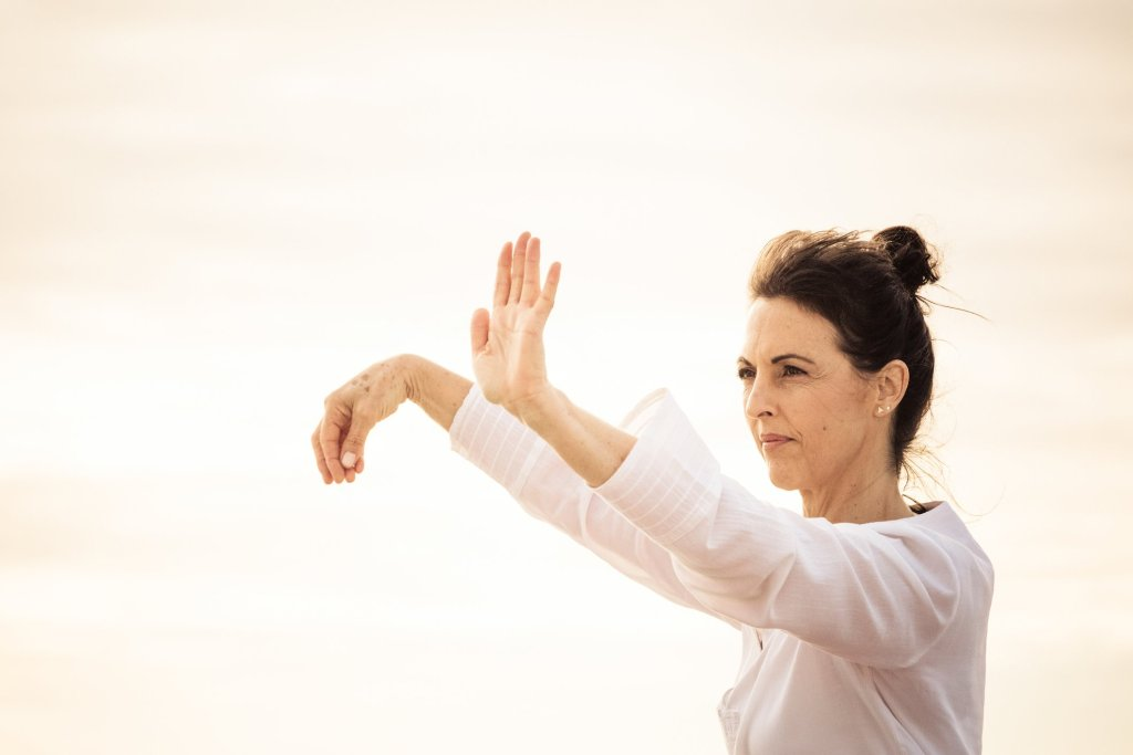 Focused woman practising traditional Wu style Tai Chi hands glide through movements golden evening sky behind her
