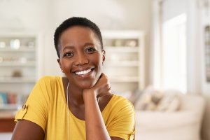 Portrait of mature woman sitting at home and looking at camera. Cheerful black girl with short hair in casual sitting in her new apartment with copy space. Satisfied woman smiling while looking at camera.