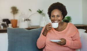 Portrait of a smiling mature African American woman drinking a cup of tea while sitting on her living room sofa at home