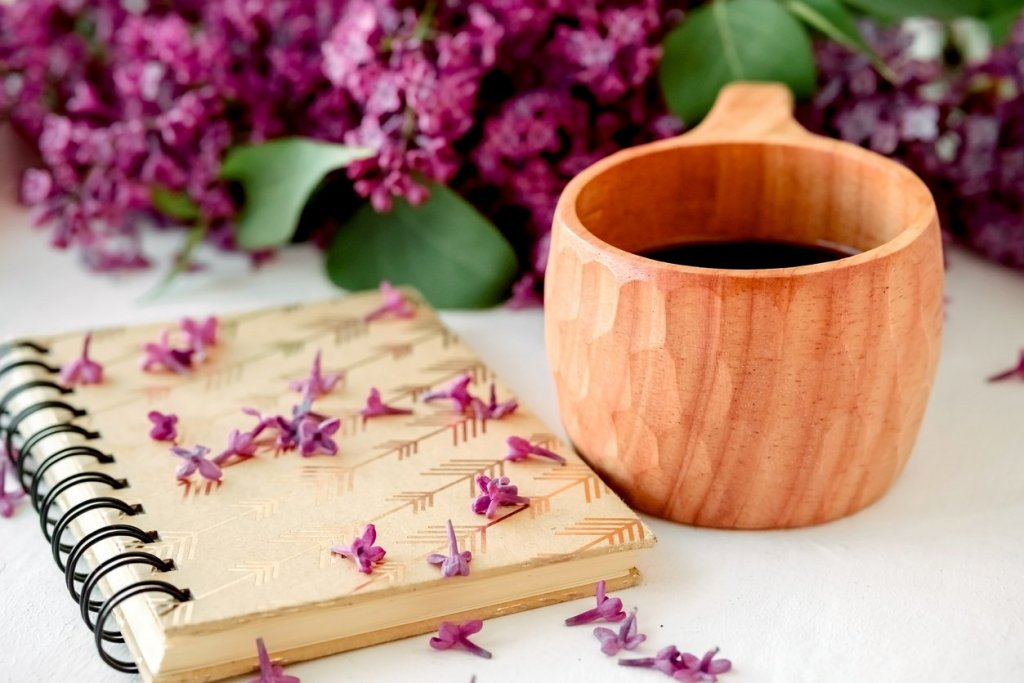 Wooden finnish cup with coffee on the table. Nearby lies a closed notebook for notes and a bouquet of lilacs. Good morning and good mood, planning a day at breakfast, concept