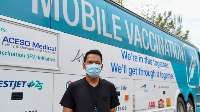 A man wearing a mask poses in front of a mobile vaccine clinic
