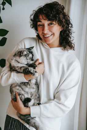 Happiness with smiling woman embracing domestic cat at home