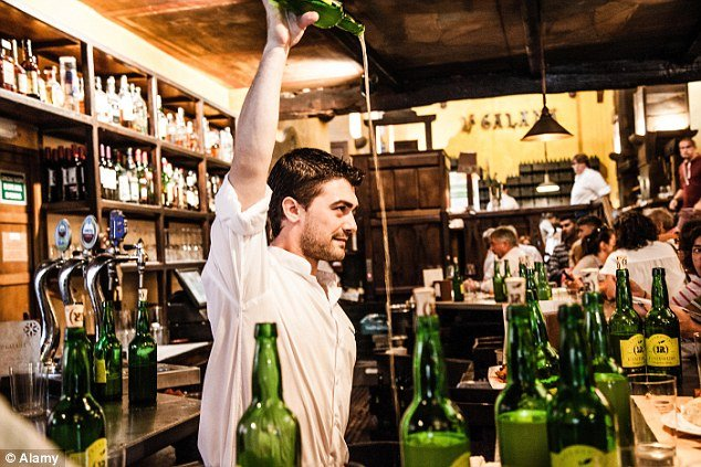 A waiter pouring cider