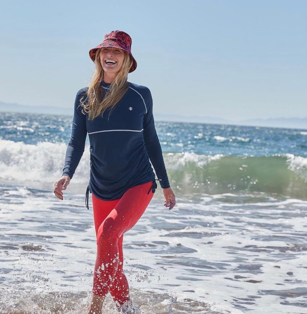 woman smiling walking through ocean waves