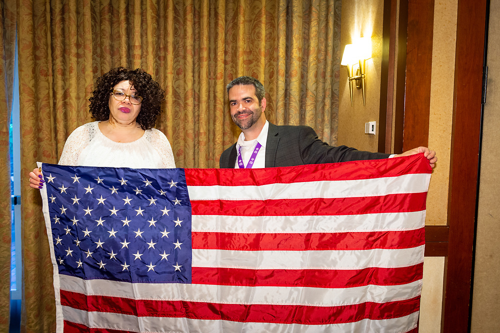 Dr. John Harris and Valarie Molyneaux, conference leaders, receive an American flag flown over the U.S. Capitol building.