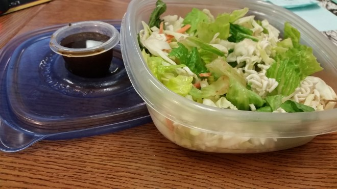Ingredients: 2-3 cups lettuce/spinach/greens, 1/4 chopped cucumber, 1-2 shredded carrots, 1/4 cup dry and crushed Ramen noodles, 2-3 tbsp Sesame Ginger salad dressing, chopped green peppers and sesame seeds for taste.
