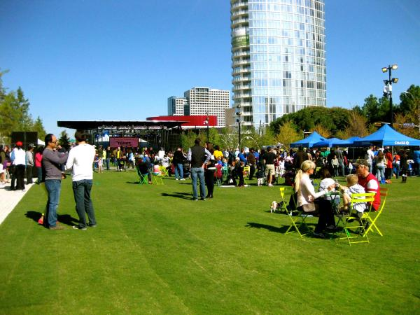 Photo of Klyde Warren Park in Dallas. Green grass and Museum Tower in the background. People walking around and eating at tables. Things to do in Dallas on Memorial Day
