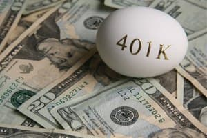 stack of money with an egg sitting on it will 401k written on the egg. Use your 401k for the downpayment for your house.