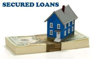 Stack of money with a house sitting on it. Use Secured Loan for the downpayment for your house