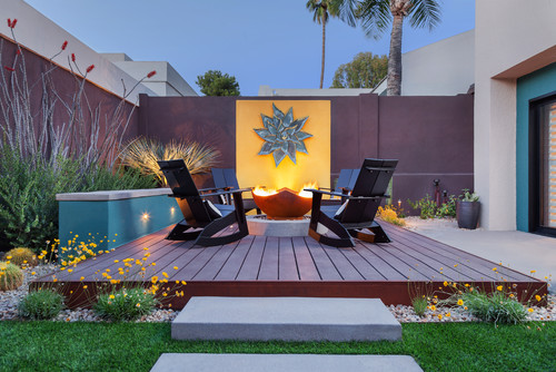 Image of a small yard with a deck, lounge chairs and a fire pit Make the most of my backyard