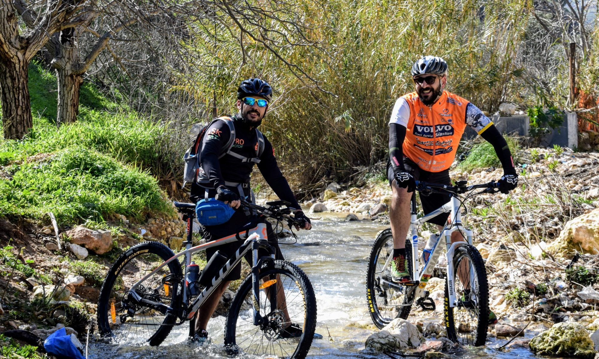 Cyclists crossing a creek on a cycling tour in Jordan