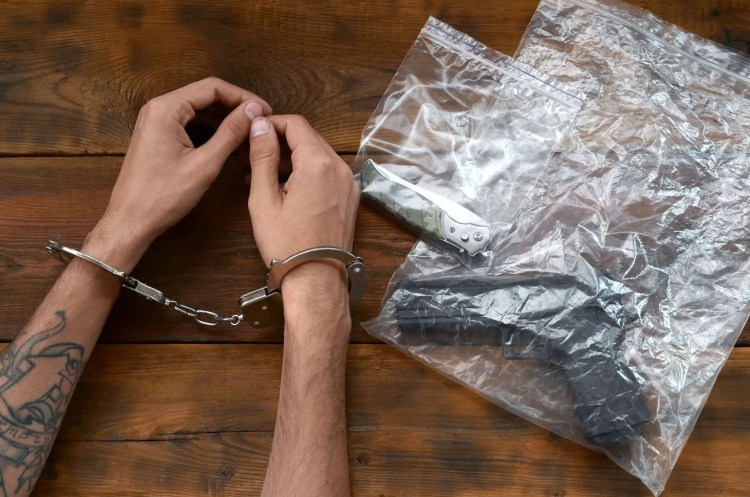 Handcuffed hands of criminal suspect on wooden table and crime scene evidence in transparent plastic