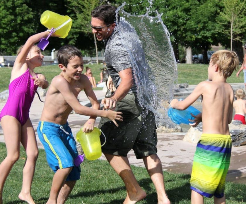 Photo of a happy laughing family having a water fight with buckets of water