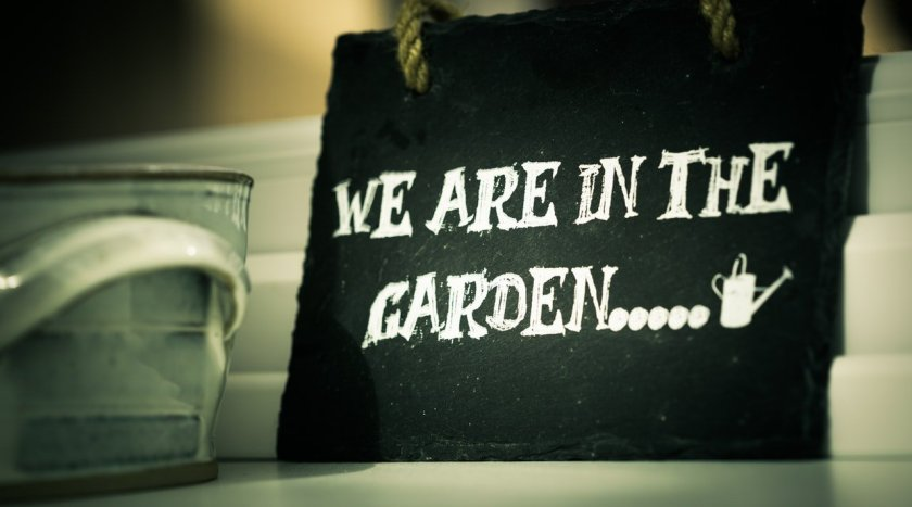 Sign saying we are in the garden. Watering can to edge of picture.