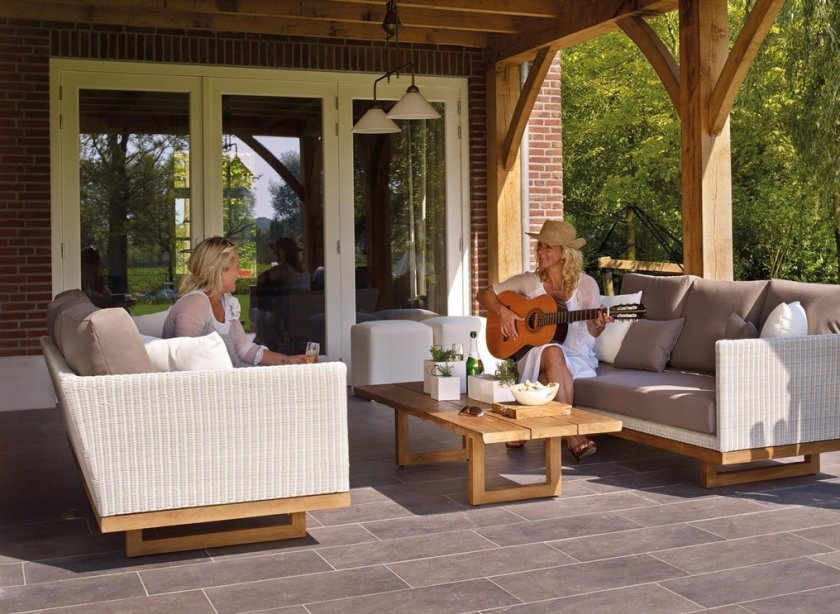 A large patio area with porch. Seating and table. Two ladies with snacks and drinks chatting, one playing guitar.