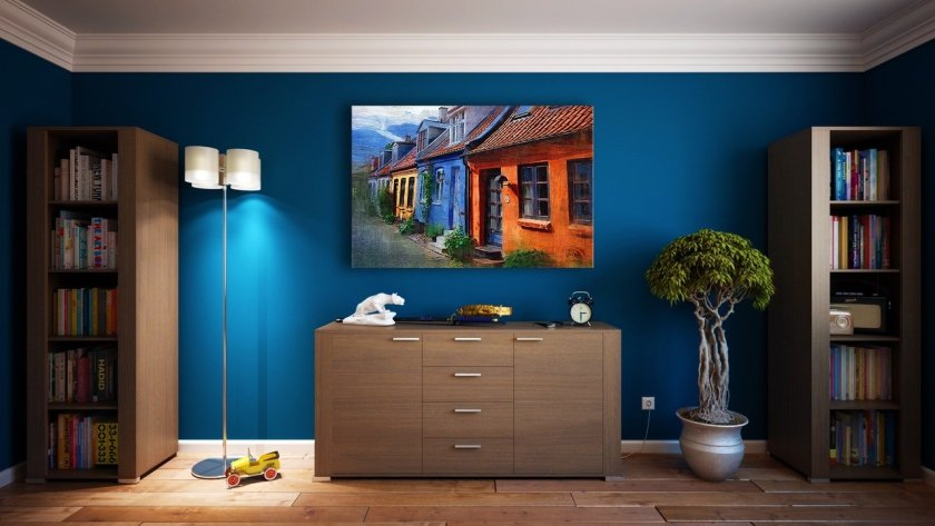 Dark blue painted wall. Picture hanging on wall. Home decor. Interior design