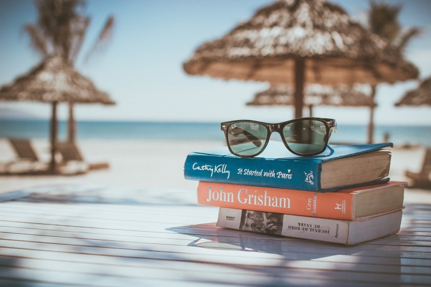 A pile of books, sunglasses on top, on table next to beach